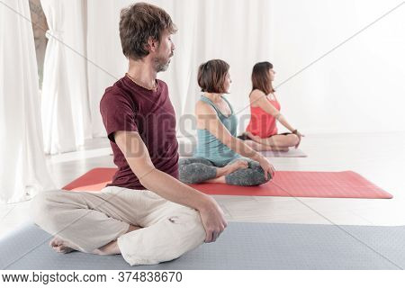 Yoga Teachers In The Lotus Position - Padmasana, Performing Yoga In The Twisting Position. Group Of