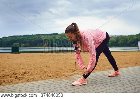 Young Jogger Stretching Her Legs After Training Outdoors. Female Athlete Doing Exercises After Runni
