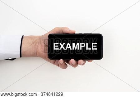 Example Word On Black Phone Screen In Male Hand Isolated On White. Business Technology Example Conce