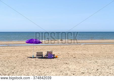 beach with umbrella and chairs