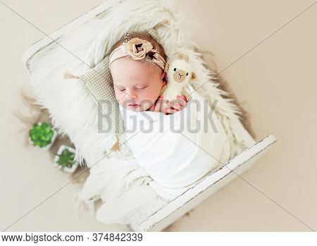 Sleeping newborn baby girl wrapped in white blanket in a small crib