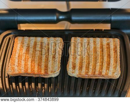 Toasted Bread Slices On The Electric Grill. Delicious Crispy Toasted Bread After Roasting. Stripes O