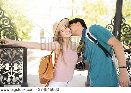 Young Man Kissing Smiling Attractive Girlfriend During Weekend Trip Together