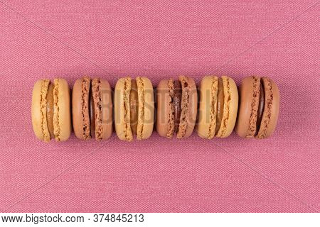 Six Coffee And Chocolated Flavoured Macaroons On Pink Vinyl Background.