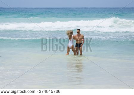 Long Haired Blonde Woman In White Swimsuit Plays With Her Husband Enjoining Their Honeymoon Vacation