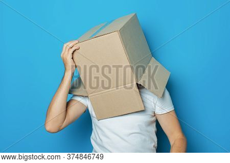 Young Man In A White T-shirt With A Cardboard Box On His Head Makes A Gesture With His Hands On A Bl