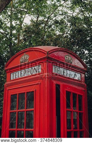 London, Uk - June 20, 2020: Low Angle View Of Red Phone Box Against Trees. Red Phone Boxes Can Be Fo