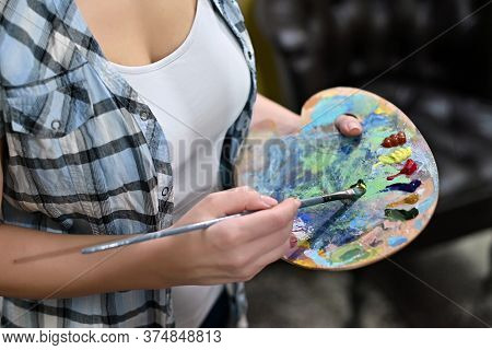 The Artist Selects A Color On The Palette. Close-up, No Face