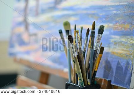 Artists Brushes On The Background Of A Painting With An Easel. Waiting For The Master