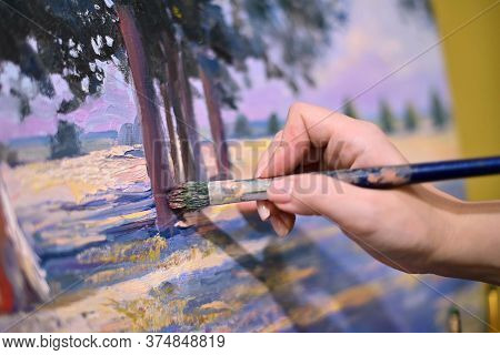 The Artist S Hand With A Brush Glides Over The Canvas Of The Painting. Close-up, Brush Strokes