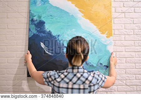 The Girl Hangs An Oil Painting On The Wall And Admires Her. View From The Back