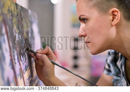 The Artist Enthusiastically And Carefully Draws Details In Her Painting. Work On The Picture With A