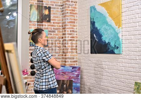 A Girl Looks At A Picture In An Art Gallery. A Woman Is Standing And Looking At A Picture On The Wal