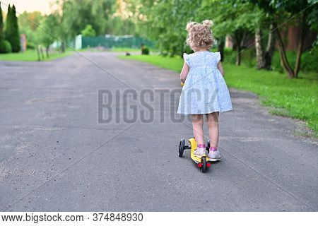 Little Girl Leaves The Camera On A Childrens Scooter. Walking On A Summer Evening In The Village