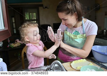 Mom With Her Little Daughter Have Fun Preparing Dinner In The Kitchen. View From The Window