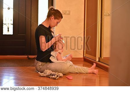 Mom Makes A Hairstyle To Her Little Daughter In The Hallway, The Sun Breaks Through The Front Door,