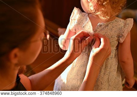 Mom Carefully Buttons The Buttons On Her Little Daughter S Dress. Evening, Sunset And Warm Tint