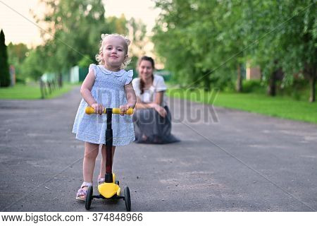 The Girl Drives Off Her Mother On A Scooter During A Summer Evening Walk