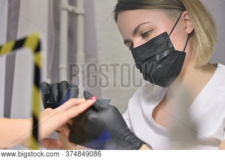 The Master Of A Nail Salon In A Protective Mask And Gloves Does The Job Of Painting The Client S Nai