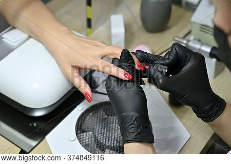 Close-up Of Applying Red Varnish To The Nails Of A Client By A Master Wearing Black Gloves