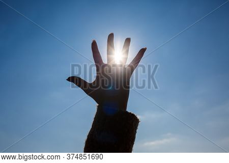 Silhouetted A Female Hand Against A Blue Sky And Bright Sun