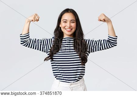 Lifestyle, People Emotions And Casual Concept. Strong And Confident Asian Woman Flex Biceps, Braggin