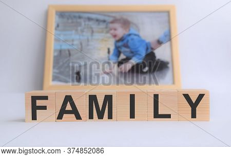 Wooden Cubes With The Inscription Family, With A Photo Of A Child In A Frame, The Concept Of Family