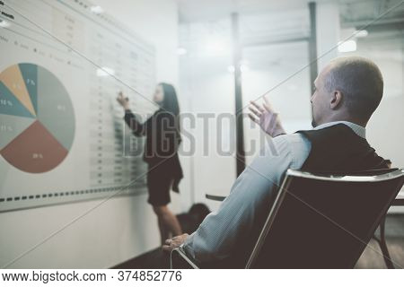 View From Behind Of A Businessman In A Boardroom On An Office Armchair Observing How His Colleague B