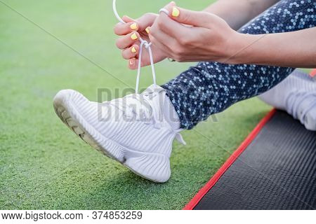 Cropped Shot Of A Young Woman Tying Her Shoelaces. Hands Of Young Woman Lacing White Sneakers. Femal