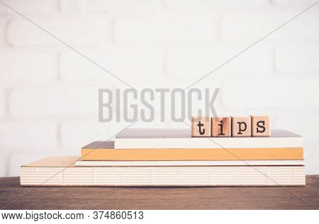 The Word Tips, Letters On Wooden Block Cubes On Top Of Books And Table With White Bricks Background,