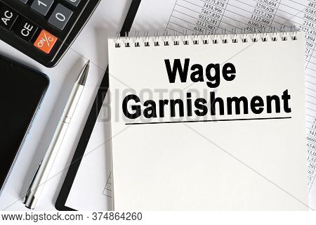 On The Table Lies A Smartphone, A Calculator And A Notebook With The Inscription- Wage Garnishment.