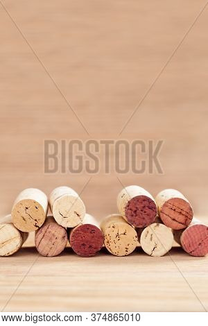 Borders Of Wine Corks On Blurred Wooden Background With Copy Space. Vertical Format.