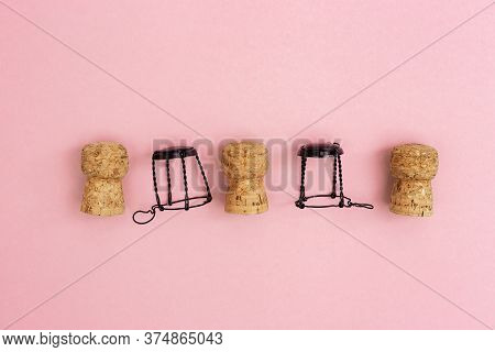 Champagne Corks And Muselets On Pink Paper Background With Copy Space. Close Up Used Wooden Stoppers