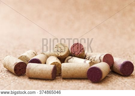 Corks From Wine Bottles Lie In A Pile On A Wooden Background. Natural Fon With Heap Of Corks From Re