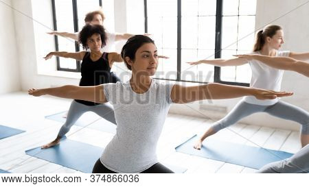 Young Fit Indian Ethnicity Woman Standing In Virabhadrasana Second Position.