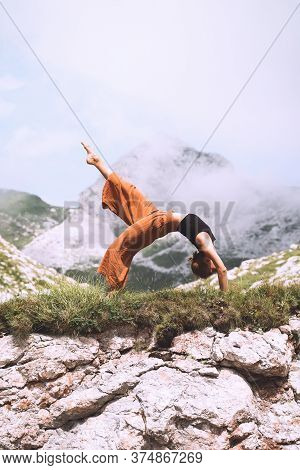 Yoga On Nature. Young Woman Is Practicing Yoga In Mountains