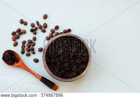 Top View Of Jar With Roasted Coffee Bean Scrub With Wooden Spoon And Sea Salt On Mint Background. Re