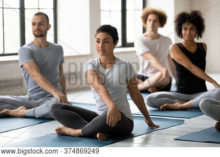 Young Mixed Race People Doing Simple Seated Twist Exercise.