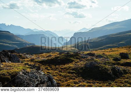 Scenic Mountain Landscape With Giant Rockies And Deep Gorge Behind Green Hill In Sunlight. Wonderful