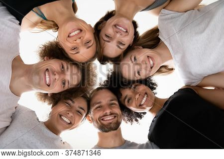 Smiling Beautiful Mixed Race People Touching Heads In Circle.