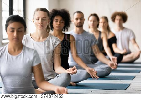 Mindful Young Mixed Race People Meditating Indoors.