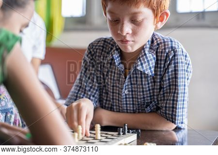 Serious Chess Player Kid Thinking And Moving Coin At Home - Concept Of Kid Concentration Of Game Dur