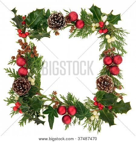 Christmas decorative border of holly, ivy, mistletoe, cedar leaf sprigs with pine cones and red baubles over white background.