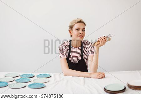 Beautiful Girl In Black Apron And Striped T-shirt Sitting At The Table With Plates And Holding Potte