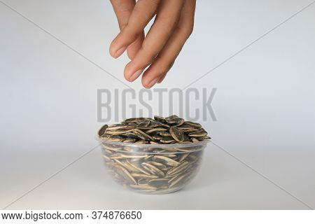Hand Pick Sunflower Seeds On Transparent Bowl Isolated On White Background.
