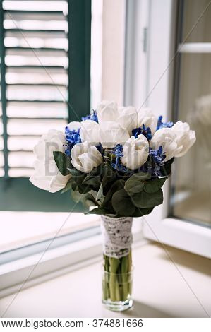 Bridal Bouquet Of White Tulips, Delphinium, Salal, Limonium And Lace Ribbons In Glass Vase On The Wi