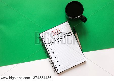 2021 New Resolution Words Written On Flat Lay Notebook, Coffee, Pen On Split Color Green And White B