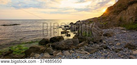 Sea Beach With Pebbles And Rocks. Beautiful Landscape With Clouds On The Sky At Sunrise. Wide Panora