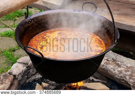 Traditional Hungarian Bogracs Goulash Soup. Cooking Dish On Open Fire In A Cauldron. Preparing Healt