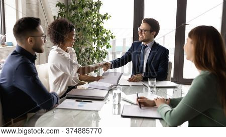 Smiling Multiethnic Businesspeople Handshake At Team Office Briefing